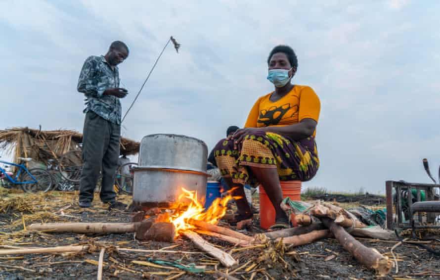 Belita Fenek prepares rice porridge over an open fire, Ntila market, Lake Chilwa