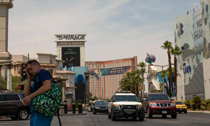 A man struggles to cross the street as the temperatures reach 116F on the strip.