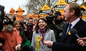 Sarah Olney and Tim Farron surrounded by members of the media