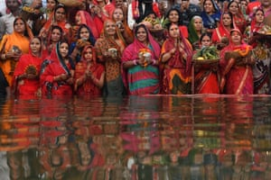 Varanasi, India. Women take part in the ritual of worshipping the sun god during the Chhath festival in the Ganges river