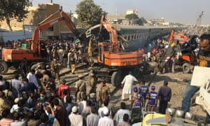 Rescuers workers use heavy machinery on the car of a train which crashed at Quaidabad station, Karachi.
