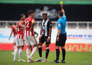 Newcastle United's Joelinton receives a yellow card from referee David Coote.