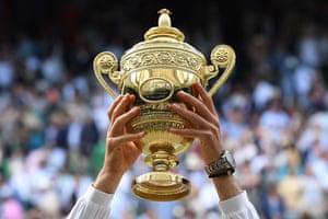 Novak Djokovic raises the winner's trophy.