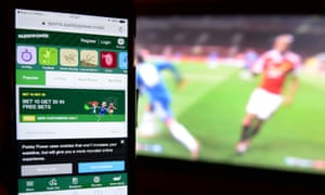 A smartphone user accesses a gambling website while watching a football match on television.