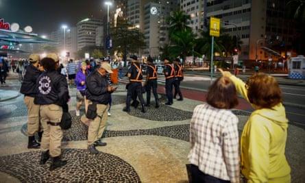 Police patrol on the Copacabana promenade in Rio de Janeiro.