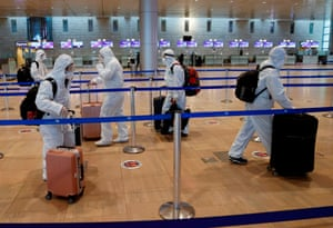 Chinese passengers wearing full protective suits and masks to protect against the COVID-19 pandemic push their luggage trolleys at the departures area at Ben-Gurion Airport in Lod, near the Israeli city of Tel Aviv, on 19 January, 2021.