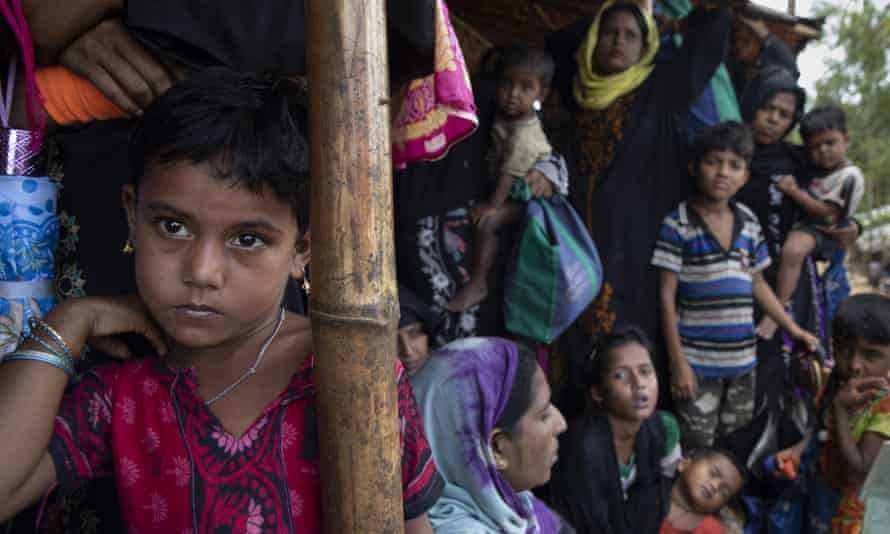 Women and children who escaped Myanmar's military crackdown on the Rohingya await food distribution at a refugee camp in Cox's Bazar, Bangladesh