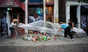 Mourners cover a memorial for those lost in Sunday morning's mass shooting in front of Ned Peppers bar in Dayton, Ohio.