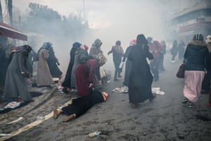 A woman assists another who has fallen as Turkish anti-riot police officers use teargas to disperse supporters