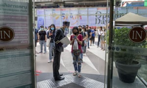 A woman displays her phone to doorman, to conform using a mobile application to help contact-tracing at the entrance to the upmarket shopping mall Siam Paragon in Bangkok, Thailand, on Sunday.