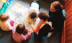 Trainee nursery worker with small children in nursery.