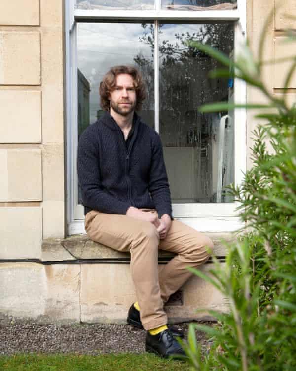 Christophe Fricker outside in a garden sitting on a windowsill