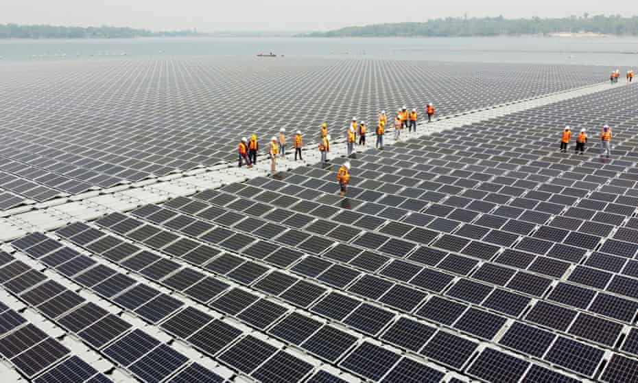 Workers walk between solar panels over the water surface of Sirindhorn Dam in Ubon Ratchathani, Thailand.