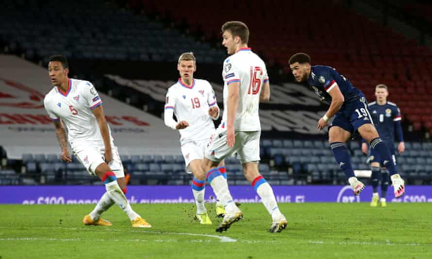 Che Adams and three Faroe Island players watch the striker's shot travel towards goal
