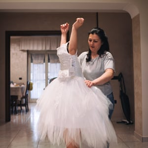 Giusy at home, being helped by her mother into the dress she has just bought.