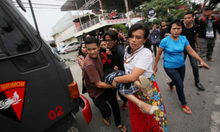 People carry an unconscious woman to an ambulance in front of a church after a would-be suicide bomber failed to detonate explosives during Sunday service in Medan.