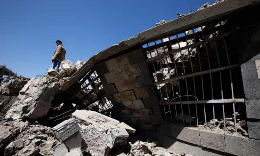 People stand among the debris of a building targeted by a Saudi-led airstrike in Sana'a