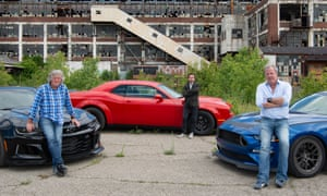 James May, Richard Hammond and Jeremy Clarkson stand beside cars outside a rundown building