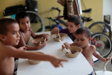 Honduran children eat at the Todo por Ellos immigrant shelter in Tapachula