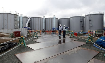 Workers stand near storage tanks for radioactive water at tsunami-crippled Fukushima Daiichi nuclear power plant in Okuma town, Fukushima prefecture, Japan