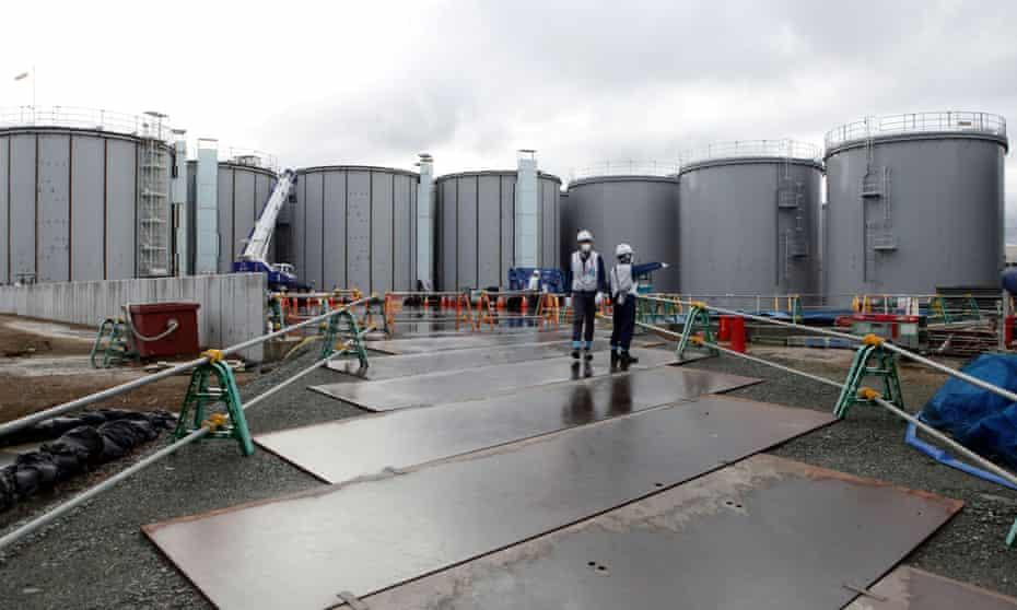 Workers stand near storage tanks for radioactive water at tsunami-crippled Fukushima Daiichi nuclear power plant in Okuma town, Fukushima prefecture, Japan
