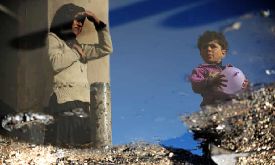 Syrian refugees are reflected in a puddle at the Bab al-Hawa camp along the Turkish border in the northwestern province of Idlib.