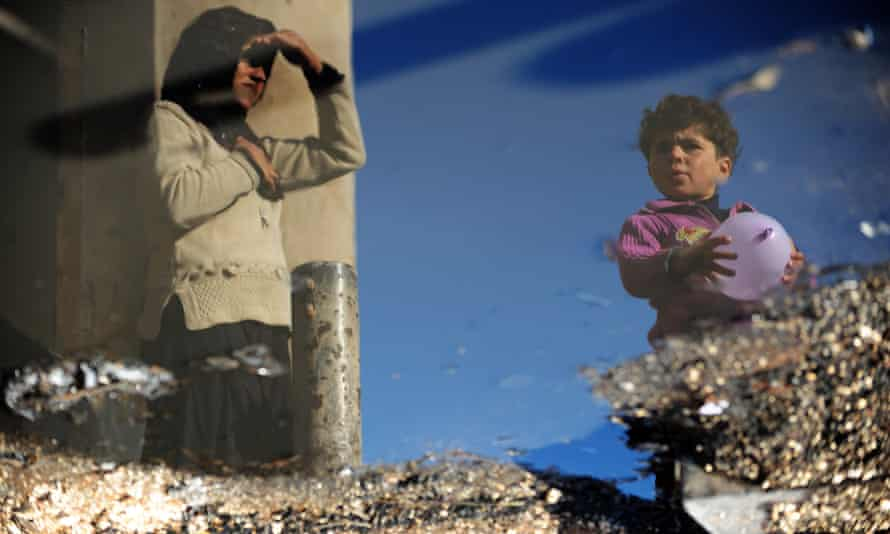 A Syrian internally displaced woman and child are reflected in a puddle of water in the Bab al-Hawa camp along the Turkish border in Idlib