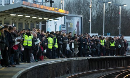 Commuters wait for a train on the platform at Clapham Common.