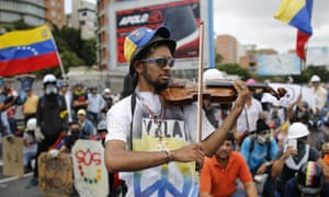 Wuilly Arteaga plays his violin before clashes with government forces at a march against Venezuela's president Nicolas Maduro in Caracas in May.