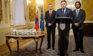 L to R: Gašpar, Fico and Kaliňák stand next to bundles of euros at the press conference.