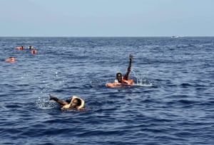 Migrants wave towards the rescuers