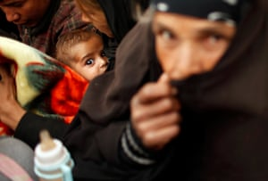 A displaced baby in Mosul, Iraq waits with his family to move to a safer location