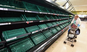 An elderly woman looks at empty shelves at a Tesco supermarket in London, March 2020.
