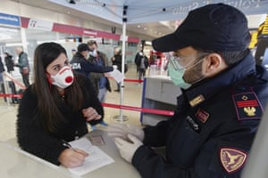 A traveller wears a face mask as she fills out a form at a checkpoint inside Rome's Termini train station