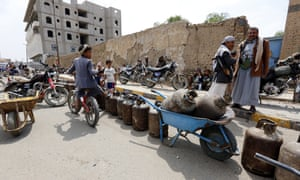Yemenis with empty cooking gas cylinders wait for gas supplies to arrive in Sana'a