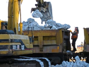 Workers unload snow from a train in Anchorage, Alaska, to cover the ground ahead of the Iditarod dog sled race. Persistent above-freezing temperatures have melted much of the local snow.