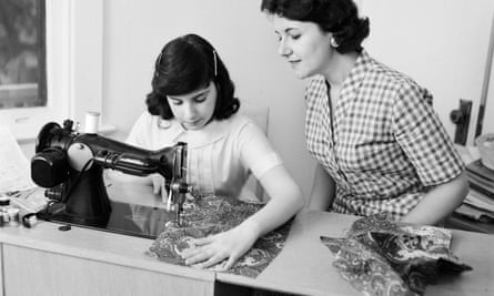Mother and daughter using a sewing machine circa 1960.
