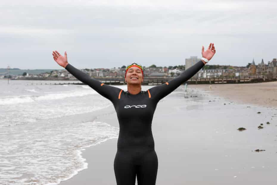 Alex Sehgal, wearing a black wetsuit, standing on the waterline with arms outstretched towards the grey sky