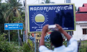 A man in Battambang province uses his smartphone to take a farewell photo of a sign for the Cambodia National Rescue party