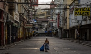 A woman walks along an empty road at the Quiapo shopping district on March 30, 2020 in Manila, Philippines.