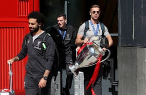 The Liverpool captain, Jordan Henderson, leaves a hotel holding the Champions League trophy in Madrid, Spain