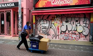 A delivery man wearing a face mask walks before a closed store at Harajuku district in Tokyo, Japan, 15 May 2020.