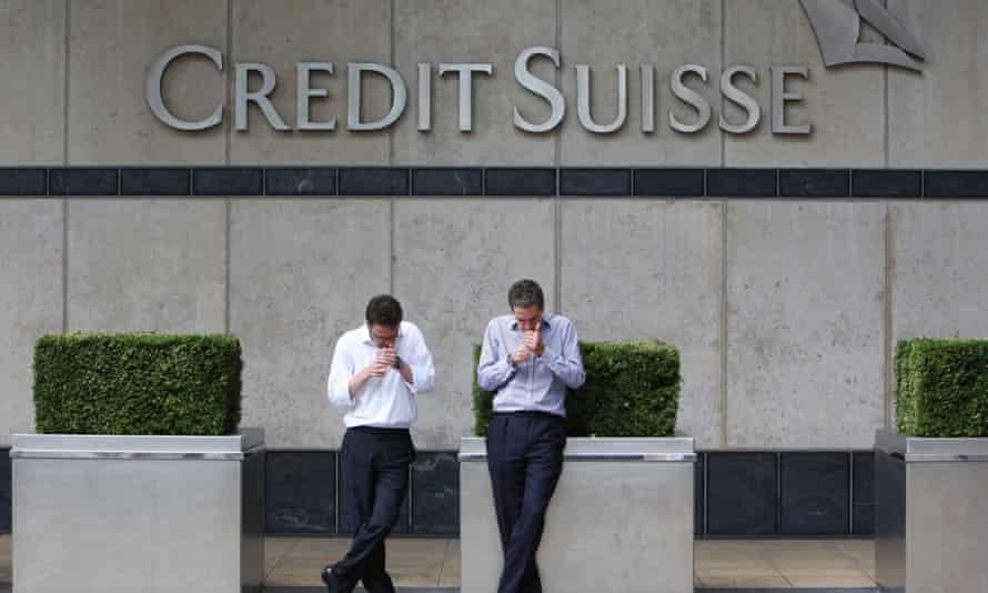 Employees take a smoke break outside the UK headquarters of Credit Suisse at Canary Wharf, London.