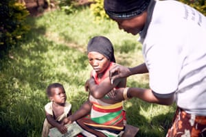 Aisha Mugoya Mutonyi, right, a volunteer member of the village health team in Mbale, Uganda, administers a contraceptive called Syana Press to a rural woman