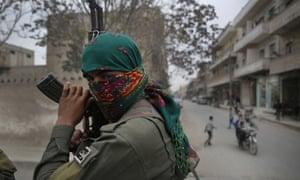 A Kurdish fighter patrols in Manbij