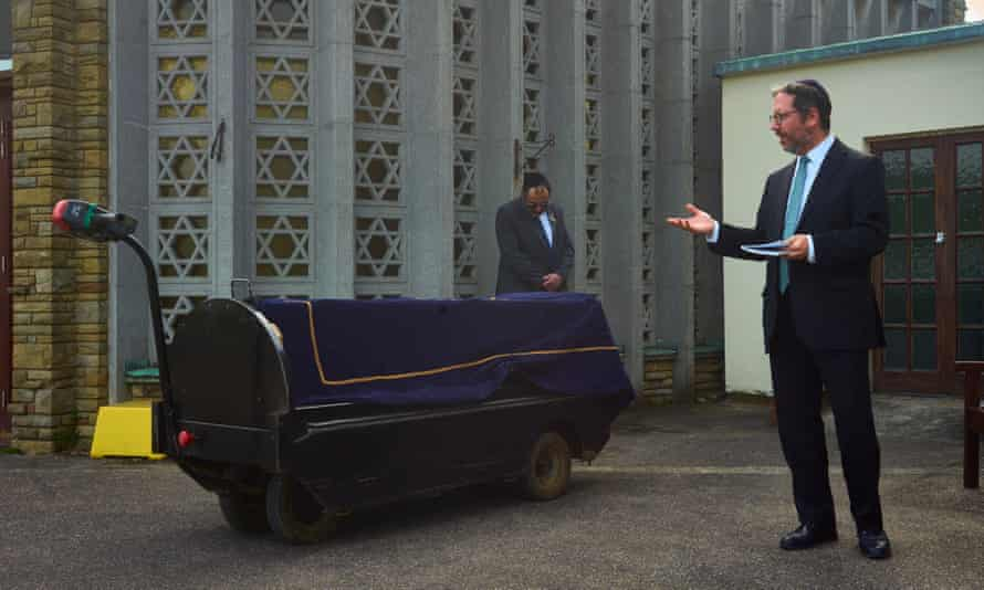 Rabbi Daniel Epstein intones funeral prayers over a shrouded coffin at Waltham Abbey cemetery, in Essex, on 7 May.