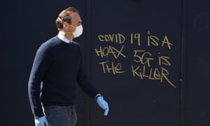 A man in a mask passes 5G conspiracy theorist graffiti in London.