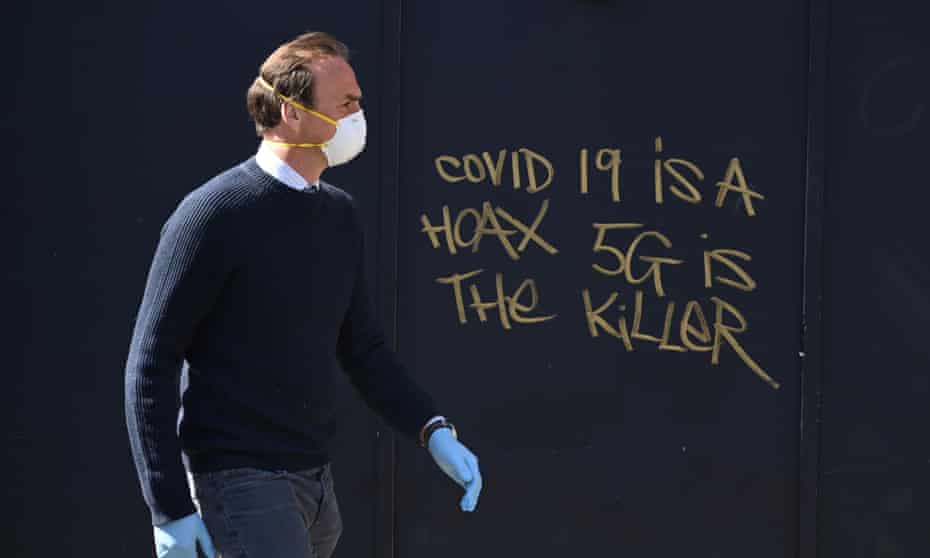 A man in a mask passes 5G conspiracy graffiti in London in April 2020.