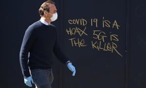 A man in a mask passes 5G conspiracy graffiti in London, Britain