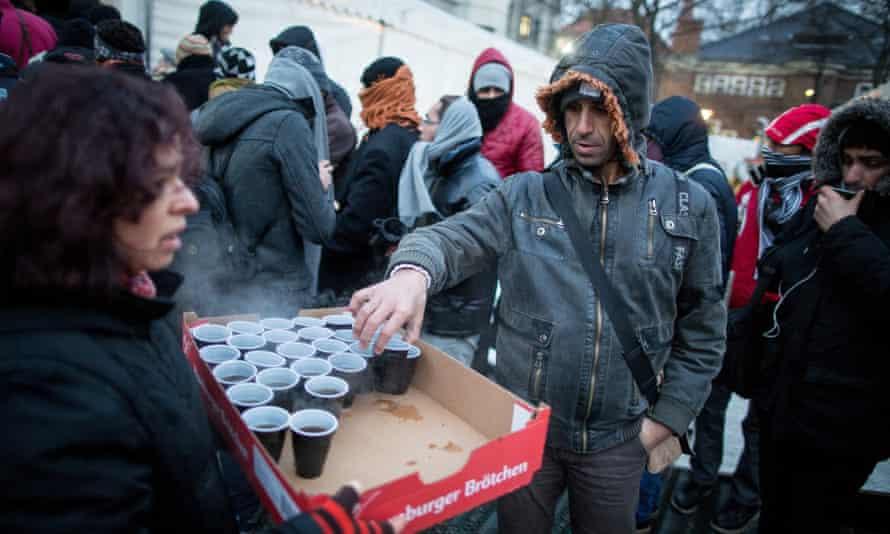A volunteer serves coffee to migrants in Berlin.